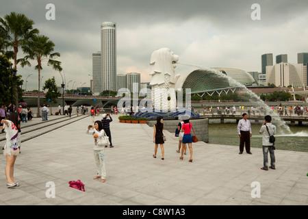 Tourists at the Merlion Park overlooking Marina Bay, Singapore - Stock Photo