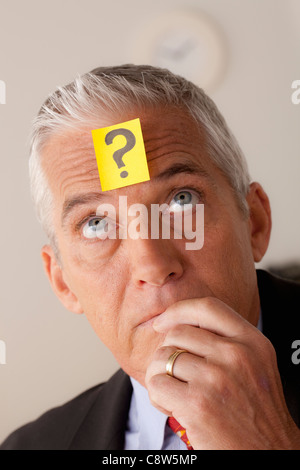 Studio portrait of senior businessman with adhesive note on forehead - Stock Photo