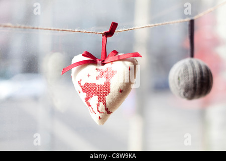 Heart Shaped Cushion And Ball Hanging On Robe - Stock Photo