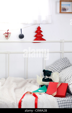 Christmas Ornaments Hanging On String And Gifts Box On Couch - Stock Photo