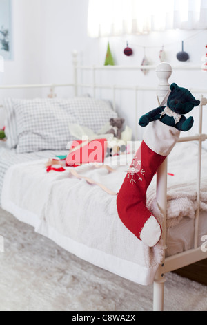 Teddy Bear In Christmas Stockings Hanging On Couch Handle And Unwrapped Gift - Stock Photo