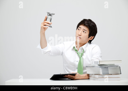 Asian Businessman Looking At Hour Glass Holding In Hand At Work - Stock Photo