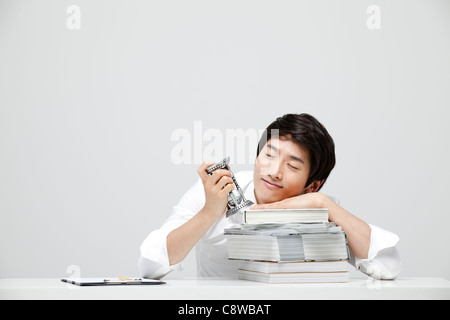 Asian Businessman Holding Hour Glass In Hand And Leaning Head On Books At Work - Stock Photo