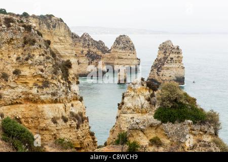 Portugal Algarve Lagos Ponta da Piedade cliffs sea seascape motor boat in bay inlet cliff - Stock Photo