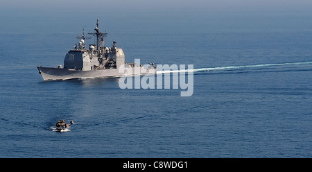 USS Chosin (CG 65) maneuvers past a fishing dhow in the Gulf of Aden while conducting counter-piracy operations. - Stock Photo