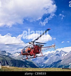 Alouette II rescue helicopter taking off from mountain helipad Zermatt Canton Valais Switzerland Europe - Stock Photo