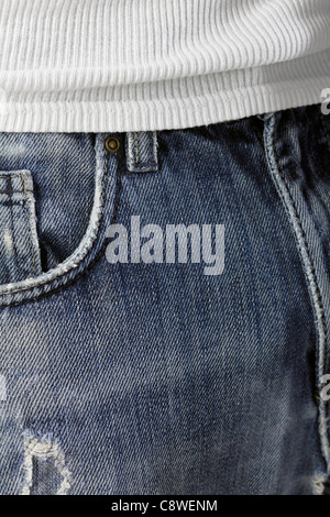 Worn blue jeans and white T-shirt as close-up. - Stock Photo