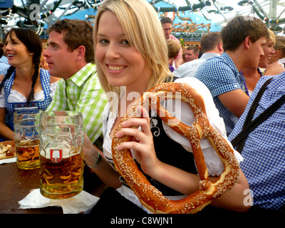 Young woman enjoying pretzel and stein of beer at Oktoberfest - Stock Photo