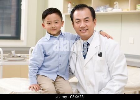 Doctor and Young Boy In Examination Room - Stock Photo