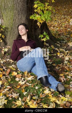 woman sleeping benath a tree in autumn