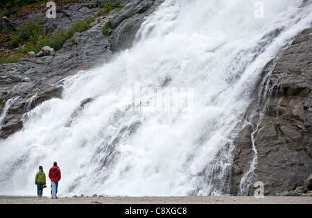 Couple contemplating the Nugget Falls. Mendenhall glacier. Juneau. Alaska. USA - Stock Photo