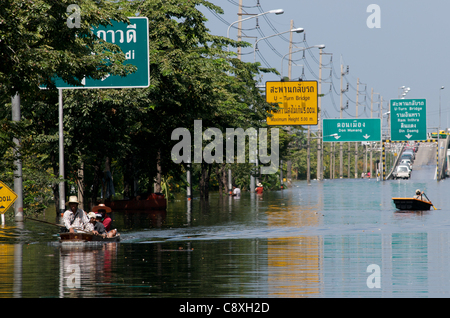 after a week of flooding, Thai refugees travel through the flood on boats. Don Muang Airport, Bangkok, Thailand - Stock Photo