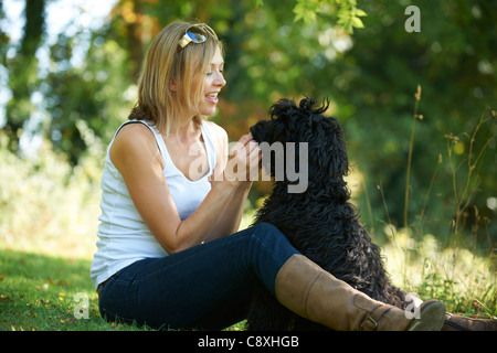 woman relaxing with black dog while on a walk in the park - Stock Photo