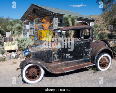 A rusted car survives the desert heat outside the General Store on Route 66 in Hackberry, Arizona - Stock Photo