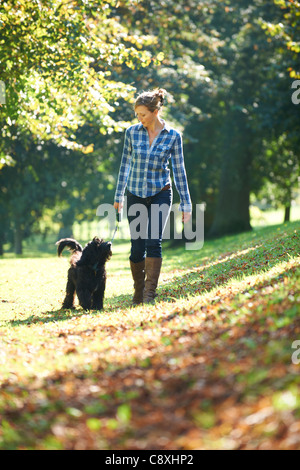 woman walking her black dog in the park on a sunny day - Stock Photo