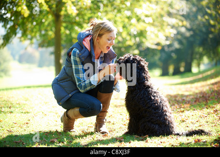 woman with black dog on a walk in the park - Stock Photo