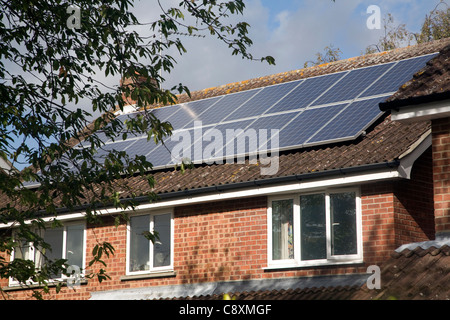 Large array of solar panels on domestic house roof - Stock Photo