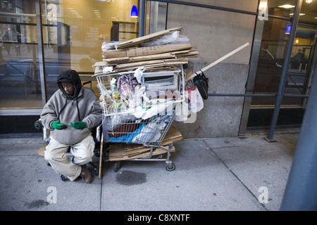 Homeless man with his possessions on 34th Street in New York City. - Stock Photo