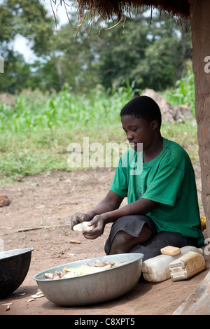A woman peels sweet potatoes harvested from her family's garden in Kibuku District, Uganda. - Stock Photo