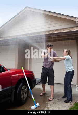 USA, Oregon, Ashland, young couple washing car in front of garage - Stock Photo