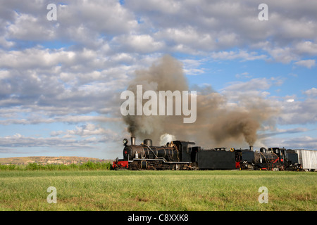 Vintage steam locomotive with billowing smoke and steam - Stock Photo