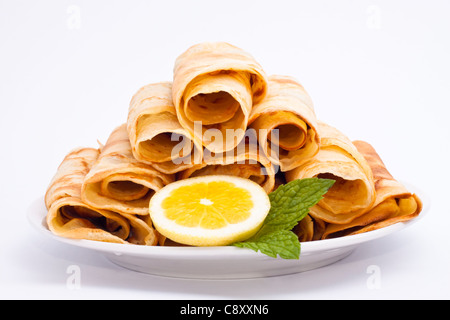 Delicious rolled crepes with lemon and mint, isolated on white background. - Stock Photo