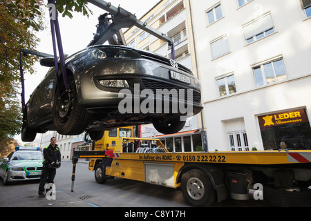 Germany, Munich, Illegally Parked Car being Towed Away - Stock Photo