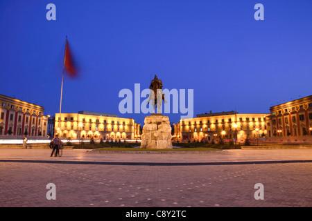 Government buildings and equestrian statue of Skanderbeg in Skanderbeg Square at dusk, central Tirana, Albania - Stock Photo