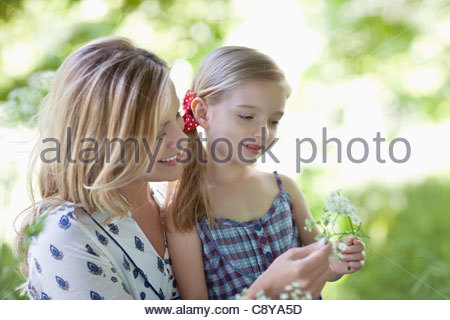 Mother and daughter examining flowers - Stock Photo