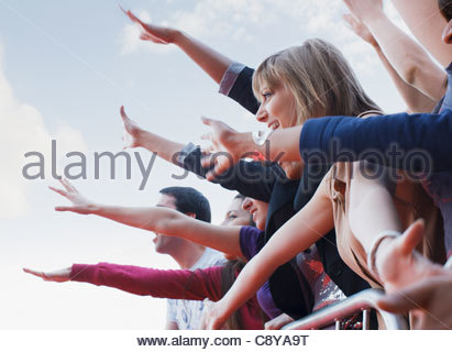 Fans waving from behind barrier - Stock Photo