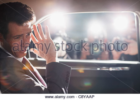 Politician shielding himself from paparazzi - Stock Photo