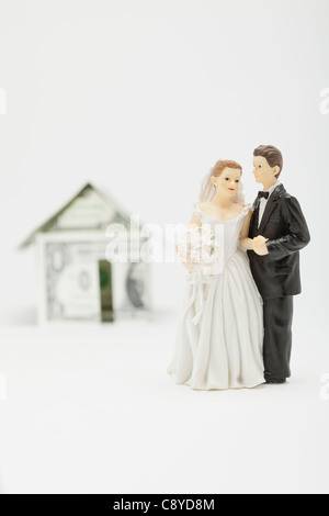 Wedding figurines in front of house model made of banknotes, studio shot - Stock Photo