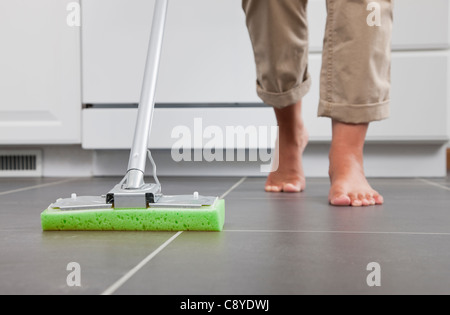 USA, Illinois, Metamora, Barefoot woman cleaning kitchen floor, low section - Stock Photo