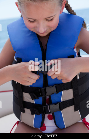 USA, Florida, St. Petersburg, Girl (10-11) fastening life jacket in speedboat - Stock Photo