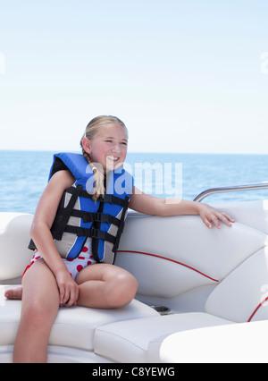 USA, Florida, St. Petersburg, Smilling girl (10-11) wearing life jacket in speedboat - Stock Photo