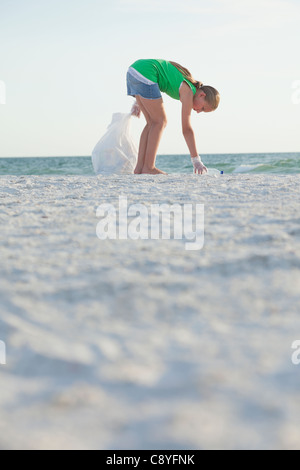 USA, Florida, St. Petersburg, Girl (10-11) cleaning beach - Stock Photo