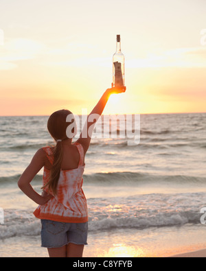 USA, Florida, St. Petersburg, Rear view of girl (10-11) holding bottle with money on beach, facing ocean - Stock Photo