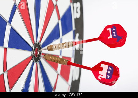 Studio shot of darts with political parties symbols in bull's-eye of dartboard - Stock Photo