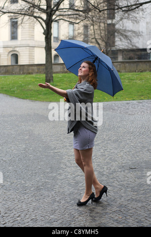young woman with umbrella enjoying the rain