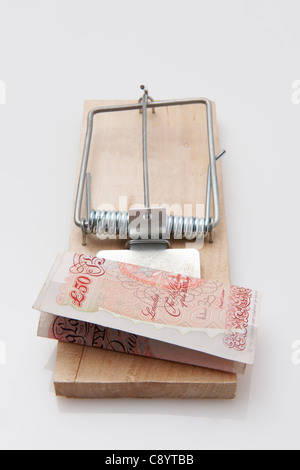 fifty pound note set on a mousetrap on white background