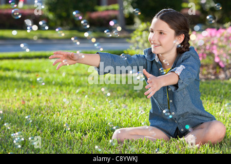 A pretty litlle girl sitting in sunshine on grass on a summer day playing and blowing bubbles - Stock Photo