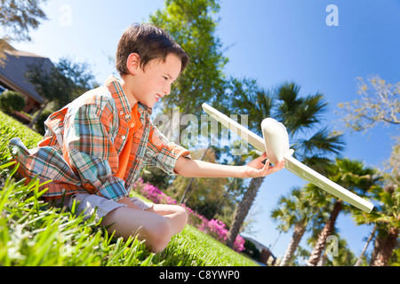 A young boy sitting on grass outside playing with a toy model airplane - Stock Photo