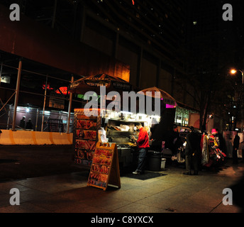 Night shot red jacket man cooking Halal food at a snack stall next to one selling clothes, West 52nd Street 7th - Stock Photo