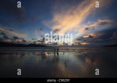 Patong beach with couple at sunset - Stock Photo