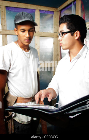 Multi ethnic construction team looking over blue prints inside house - Stock Photo