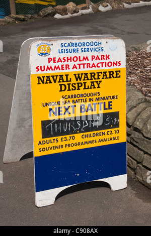 Advertising board for Naval Warfare Display, using model boats, on lake in Peasholm Park, Scarborough