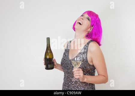 Funny photo of Caucasian woman wearing bright pink party wig and sparkling dress, drinking wine - Stock Photo