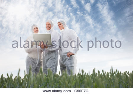 Scientists in protective gear using laptop outdoors - Stock Photo