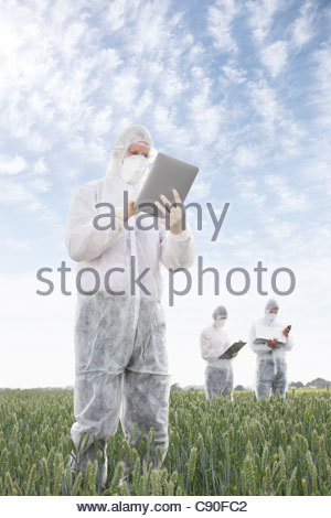 Scientist in protective gear using tablet computer - Stock Photo