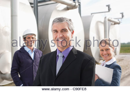 Business people standing beside tanks outdoors - Stock Photo